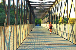 Runner crossing a metal bridge at sunrise during morning trainin